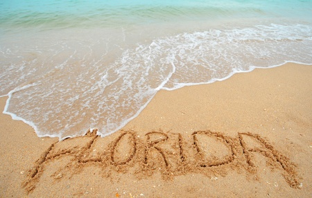 A warm tropical beach with blue water and waves and Florida written in the sand