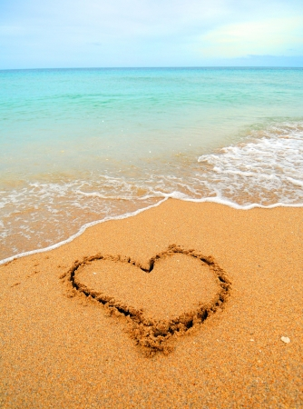 written:  A warm tropical beach with blue water and waves and a heart drawn in the sand