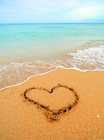 Een warm tropisch strand met blauw water en golven en een hart getrokken in het zand