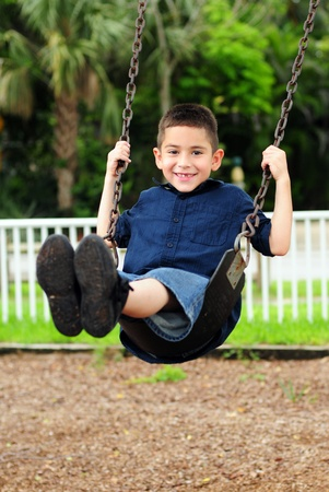 Happy young boy sitting swinging on swing at outdoor park photo