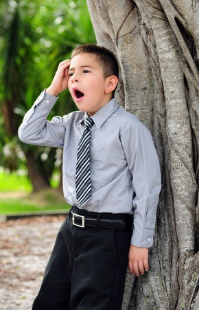 Young boy who is bored dressed in suit