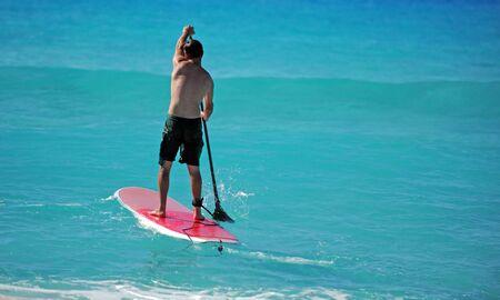Man on a cabo Paddle Junta remar hacia el oc�ano en aguas tropicales