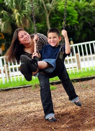 Mooie moeder duwt haar zoon op een schommel in een park buiten Stockfoto