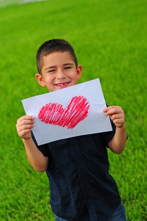 Young boy holding up a gift of a red heart drawing photo