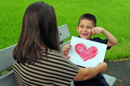 Ni�o dando a su mam� un dibujo del coraz�n de un presente