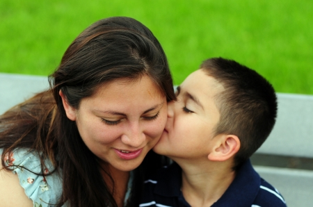 latina female: Son who loves his mother is kissing her on the cheek