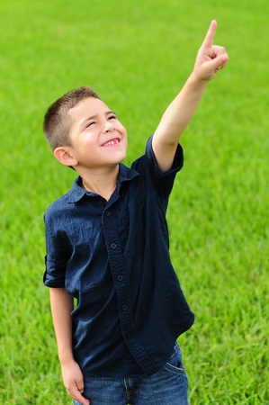 Cute young boy in blue shirt and jeans pointing up at sky