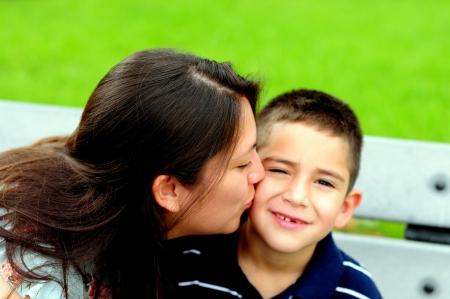 ni�os latinos: Madre besando a su hijo en la mejilla