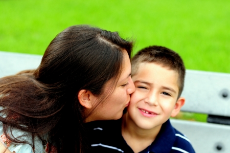 latino: Mother kissing her young son on the cheek