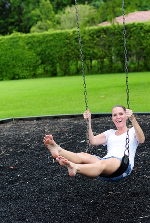 young woman on swing at playground enjoying summer