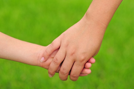 close together: A young mother and child holding hands Stock Photo