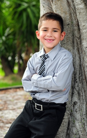 Happy Young boy leaning in business attire smiling with missing tooth photo