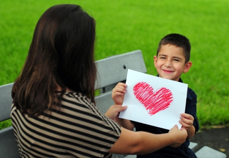 young boy giving his mother a heart drawing for a present Banque d'images