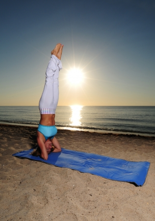 Woman doing handstand yoga pose on beach during a beautiful sunrise photo