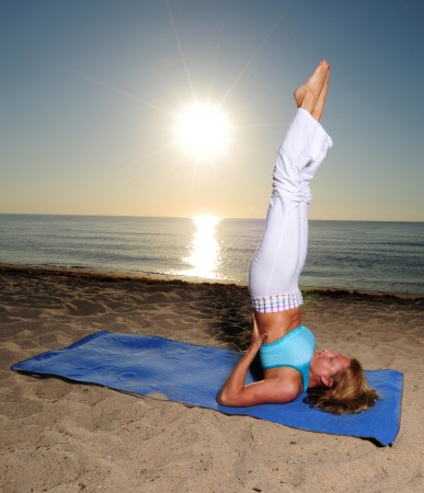 yogini: Woman doing shoulder stand yoga pose on beach during a beautiful sunrise Stock Photo