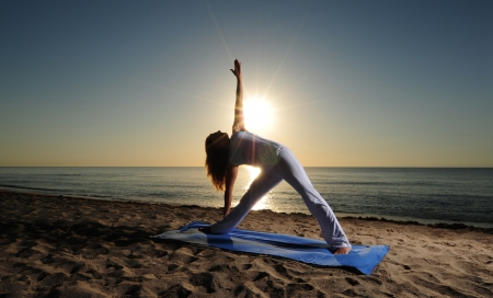 Woman doing Triangle Pose (Trikonasana) yoga  on beach during a beautiful sunrise