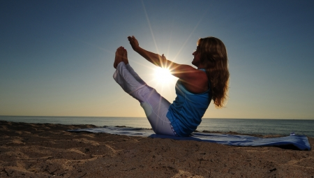 Woman doing full boat yoga pose on beach with sunrise photo