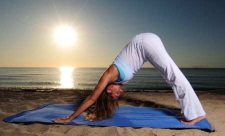 Woman doing Downward Facing Dog (Adho Mukha Svanasana) yoga pose on beach during sunrise photo