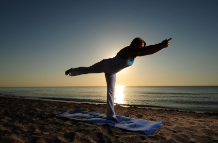 virabhadrasana: Woman doing yoga Warrior Pose III (Virabhadrasana III) on beach during a beautiful sunrise