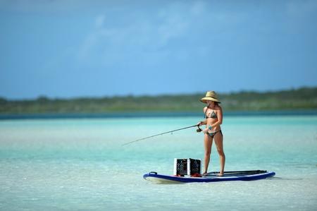 fishing gear: Beautiful woman in bikini fishing and paddleboarding in the bahamas Stock Photo