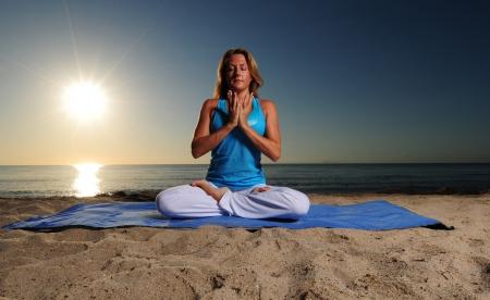 Mujer que hace la posici�n de loto completa para la meditaci�n en la playa durante un hermoso amanecer