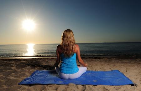 Meditation on beach with ocean and beautiful sunrise