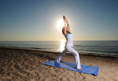 Woman doing yoga pose on beach with sunburst photo