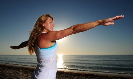 Woman doing Warrior Pose II (Virabhadrasana II) yoga pose on beach during a beautiful sunrise photo