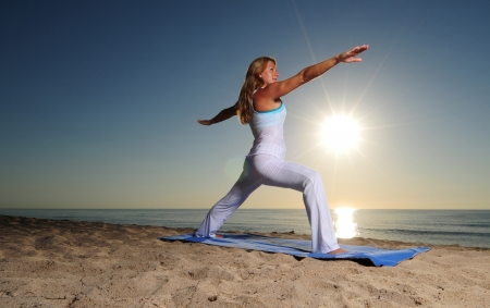 virabhadrasana: Woman doing Warrior Pose II (Virabhadrasana II) yoga pose on beach