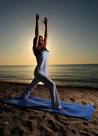 yogini: Woman doing yoga pose on beautiful beach Stock Photo