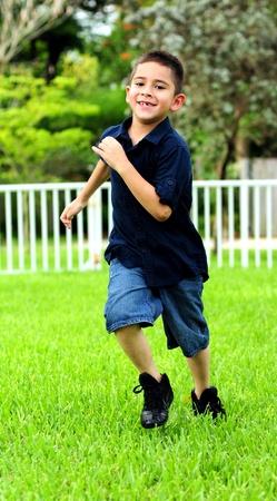 Kind loopt op gras voor de uitoefening en lacht een tandeloze grijns