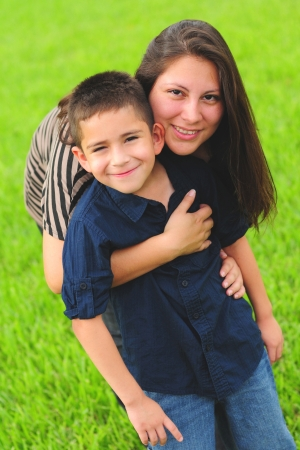 Beautiful mother hugging son outdoors in summer Stockfoto