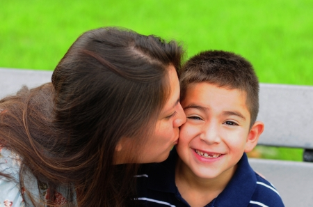 women kissing: Loving mother kissing her attractive young son on the cheek Stock Photo