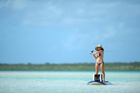 resting rod fishing: Beautiful woman casting fishing rod while paddleboarding in the Caribbean Stock Photo