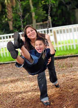 ni�o empujando: Chico joven balance�ndose en el columpio, mientras que la madre lo empuja Foto de archivo