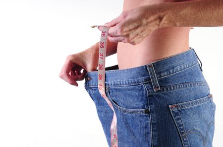 healthy young woman with measuring tape and loose jeans demonstrating weight loss photo