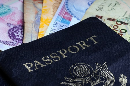 An international traveler concept with foreign money, currency and a passport photo