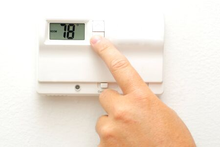 hands in the air: A hand turning down the thermostat for an energy savings concept