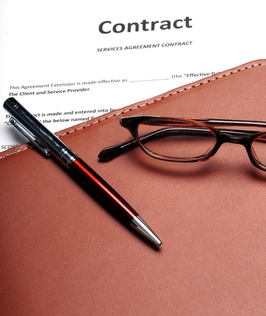 A business contract with reading glasses and a pen photo