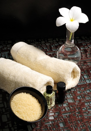 bath salts: Essential oils, bath salts, towels and a frangipani flower Stock Photo