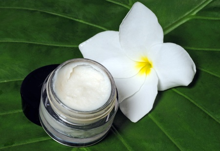 Eye cream on a natural leaf with a frangipani flower Stock Photo