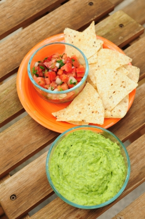 Guacamole dip with chips and salsa photo