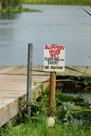 Slippery When Wet sign at dock near pond photo