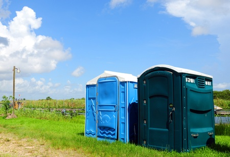 Green and blue outhouses near a river