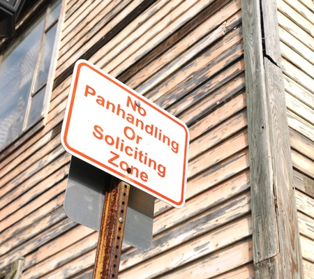 soliciting: no panhandling or soliciting zone sign near wooden building Stock Photo