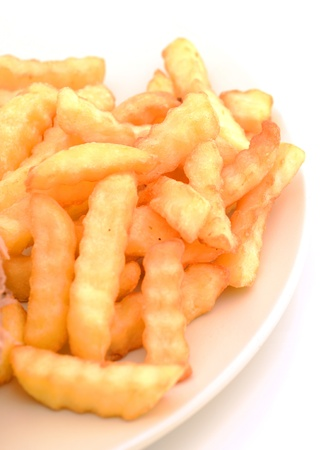 crinkle cut french fries on a plate with nobody Imagens