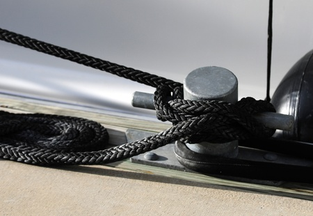 black rope tied around cleat on a boat photo