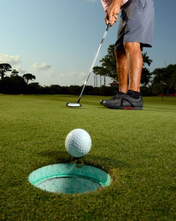 hole: Golfer putting ball in hole on golf course