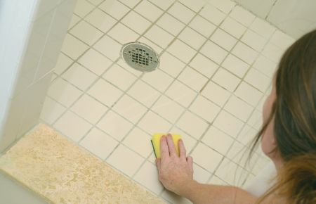 woman scrubbing soap scum from a dirty shower floor with scour pad Banque d'images