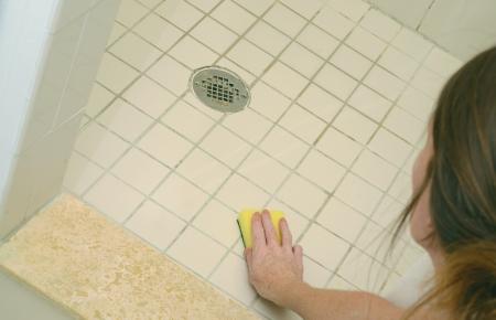 vrouw schrobben zeepresten uit een vuile douche vloer met schuren pad Stockfoto